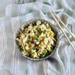 bowl of fried rice containing eggs, soy sauce, green onions and salt and pepper to taste
